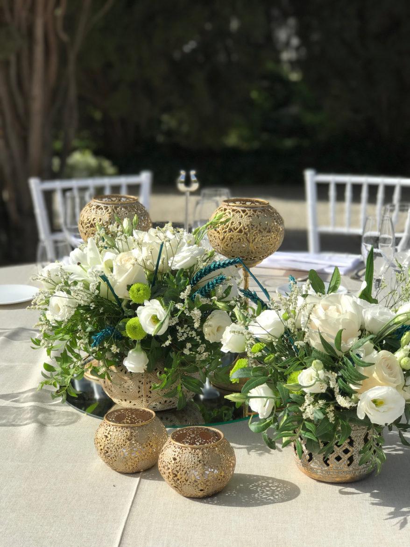 Centro de mesa con flores y velas con accesorios dorados